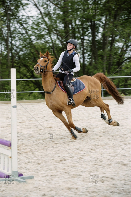 Woman with horse on show jumping course