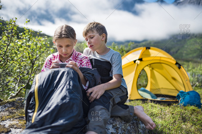 Brother and sister using cell phone in front of tent