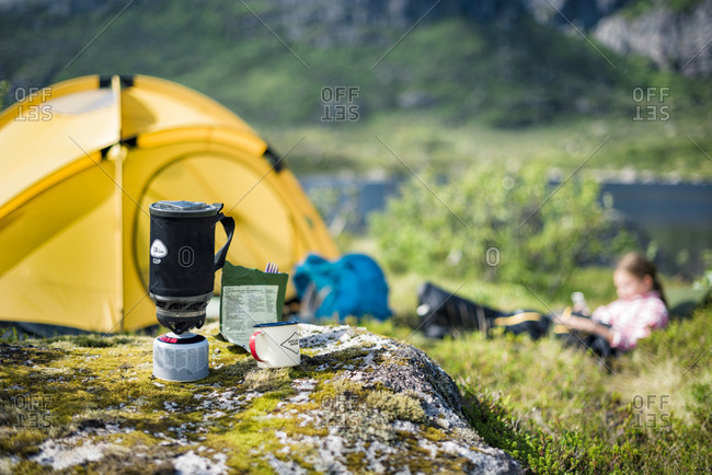 Camping stove, tent and girl on background