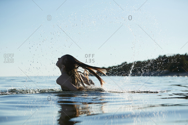 Girl tossing hair in water