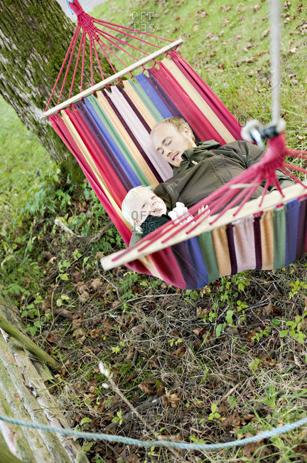 Man resting in hammock with son