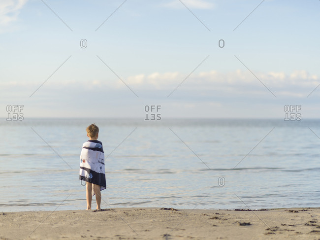 Boy wrapped in towel on beach