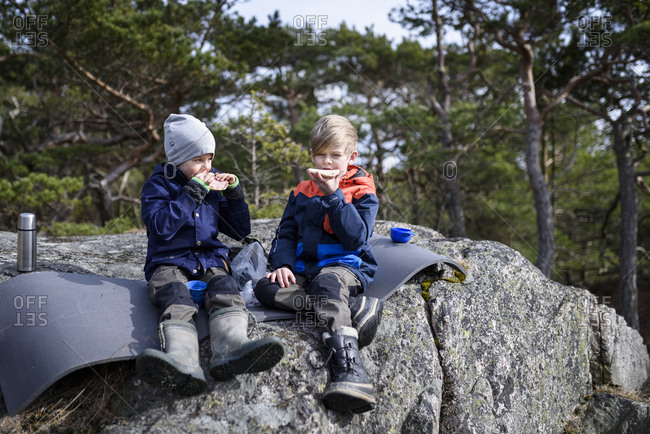 Boys sitting on rock and eating