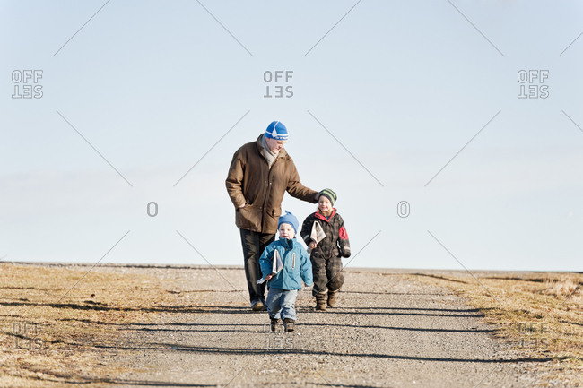 Grandfather and grandchildren walking along rural road