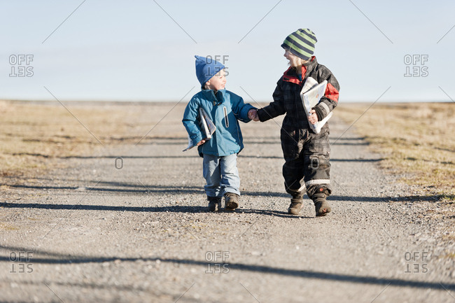 Brother and sister carrying newspaper