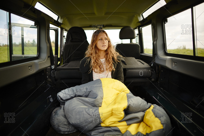 Young woman with sleeping bag sitting in off-road vehicle