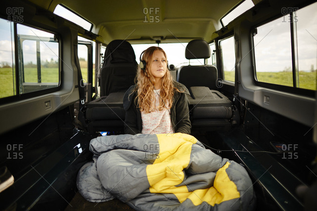 Young woman with sleeping bag and headphones in off-road vehicle