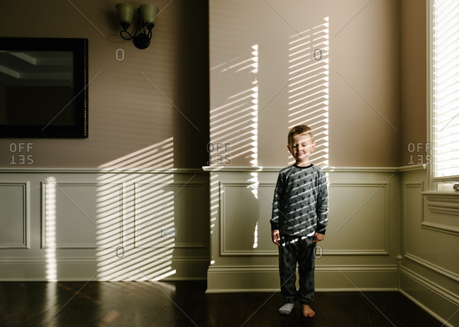 Boy in light through blinds in home