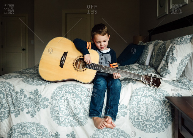 Boy playing guitar on a bed
