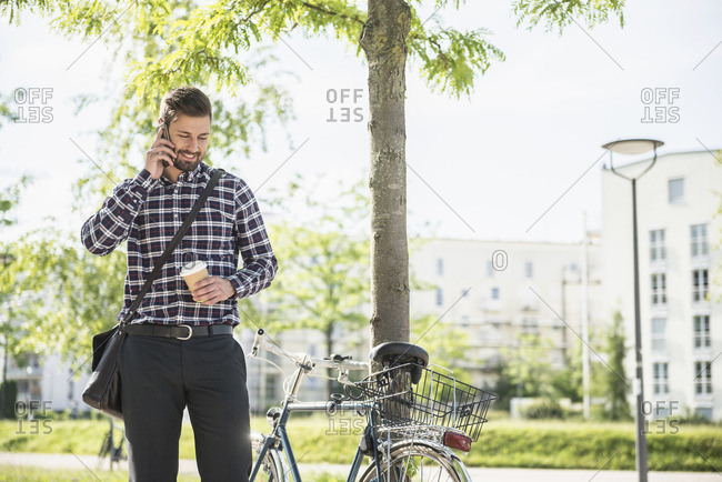 Young man talking on the mobile phone and drinking coffee, Munich, Bavaria, Germany