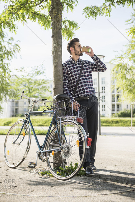 Young man leaning against a tree and drinking coffee, Munich, Bavaria, Germany