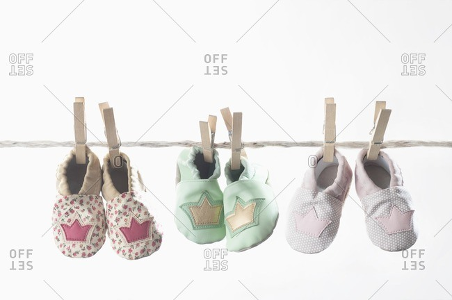 Three pairs of baby shoes hanging on clothes line, Bavaria, Germany