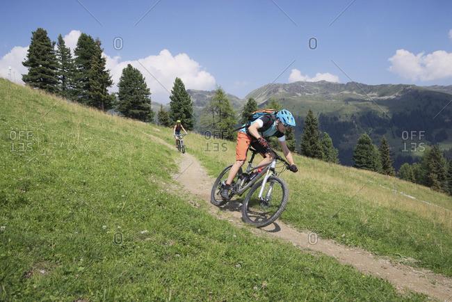 Two mountain bikers riding on downhill in alpine landscape, Zillertal, Tyrol, Austria