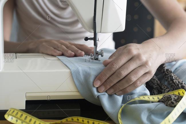Female dressmaker stitching cloth on sewing machine, Freiburg im Breisgau, Baden-Wurttemberg, Germany
