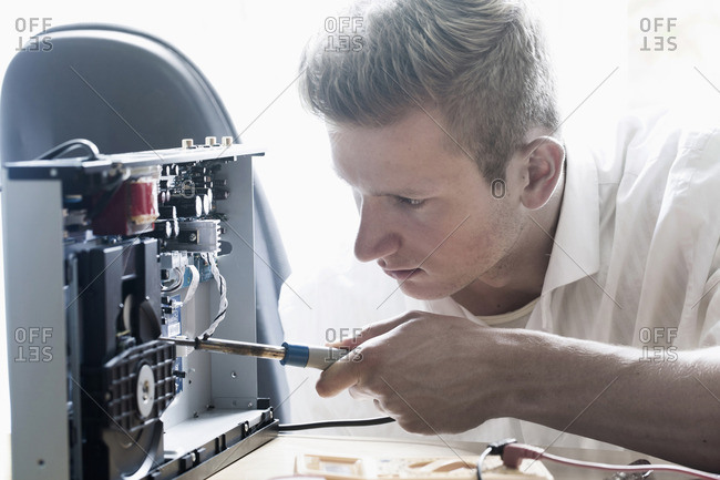 Engineer repairing CD player in workshop, Freiburg Im Breisgau, Baden-Wurttemberg, Germany
