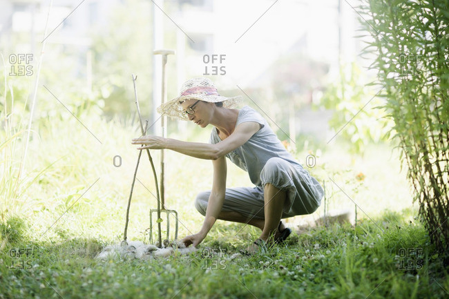 Mature woman working in urban garden, Freiburg im Breisgau, Baden-Wurttemberg, Germany