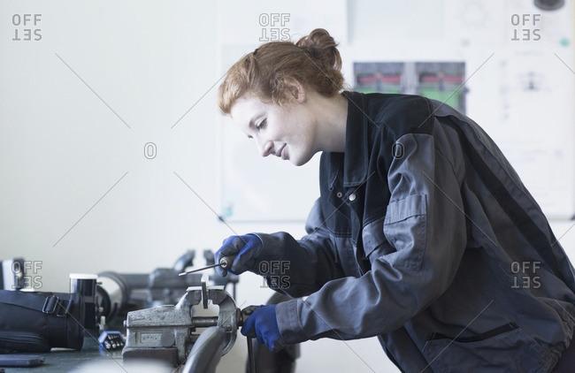 Young female engineer using vise grip tool in an industrial plant, Freiburg im Breisgau, Baden-Wurttemberg, Germany