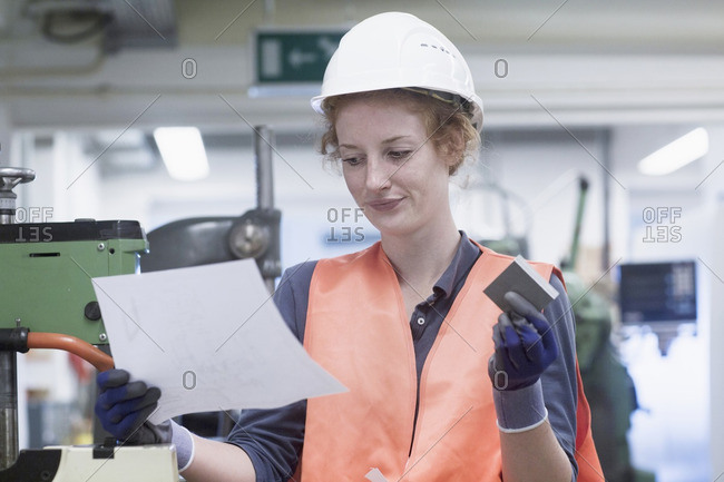 Young female engineer holding machine part with paper in an industrial plant, Freiburg im Breisgau, Baden-Wurttemberg, Germany