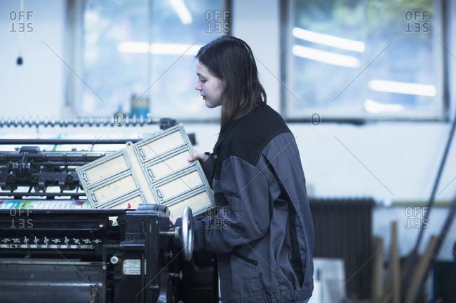 Print worker adjusting printing machine in an industry, Freiburg im Breisgau, Baden-Wurttemberg, Germany