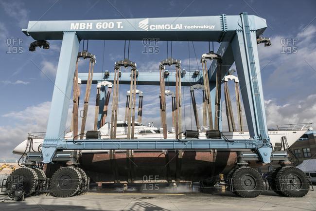 Viareggio, Italy - November 17, 2016: Yacht hoisted onto truck for transport in shipyard