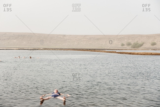 Sal, Cape Verde - December 29, 2016: Person floating in salt lake at the Pedra Lume Salt Crater