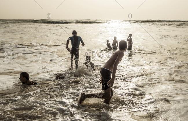 Boa Vista, Cape Verde - December 30, 2016: Young men splashing in the water at beach