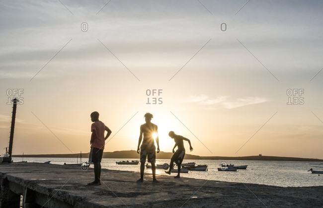 Boa Vista, Cape Verde - January 3, 2017: Boys playing football on pier in Sal Rei