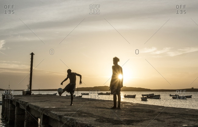Boa Vista, Cape Verde - January 3, 2017: Two boys playing football together on pier in Sal Rei