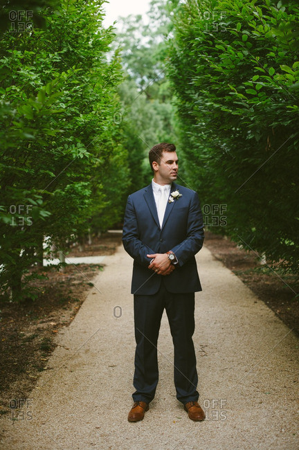 Groom looking away on secluded path
