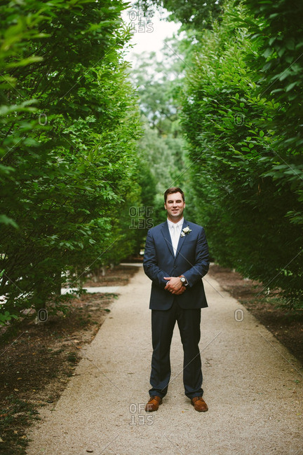 Smiling groom on secluded path