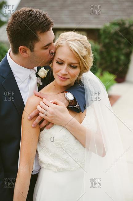 Groom kissing bride standing outside
