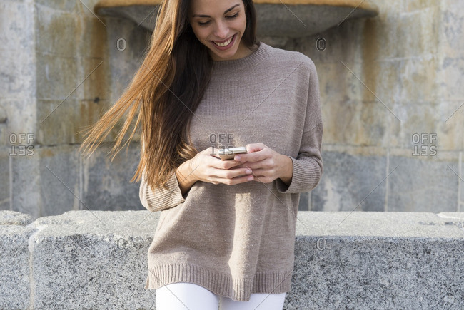 Smiling woman using her phone while leaning against a wall with an old fountain in the background in Boadilla del Monte, Madrid, Spain