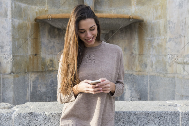 Smiling woman using her phone while leaning against a wall with a historic fountain in the background in Boadilla del Monte, Madrid, Spain
