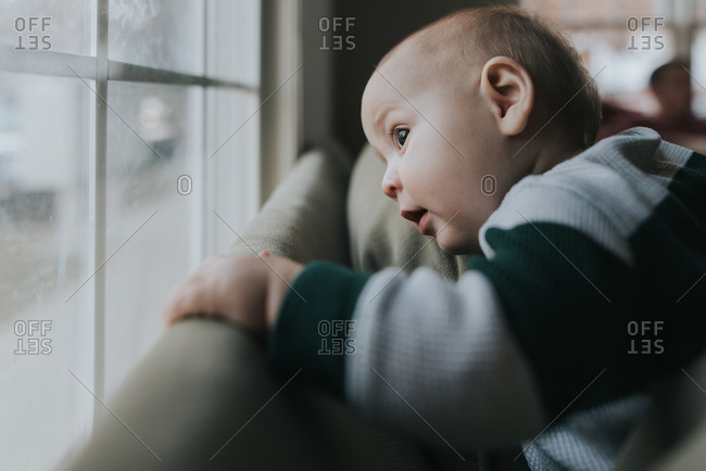 Baby boy gazes curiously out window
