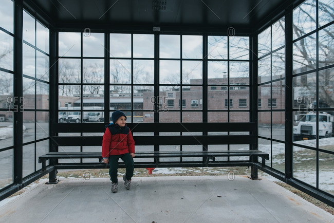 Child sitting on bench in bus shelter