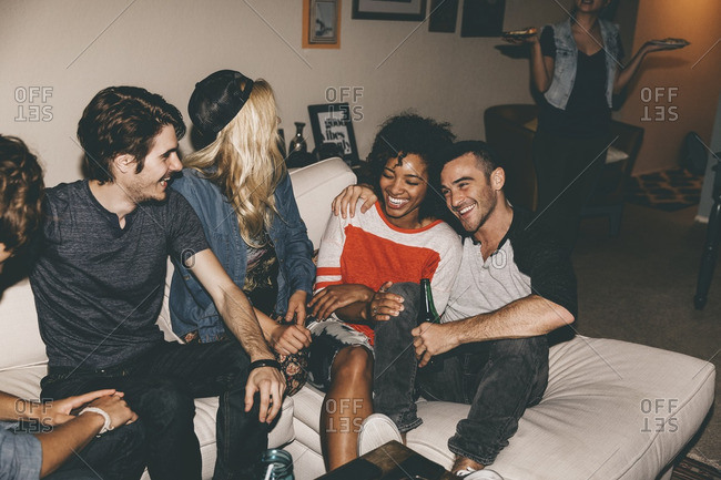 Cheerful multiethnic friends enjoying while sitting on sofa during house party