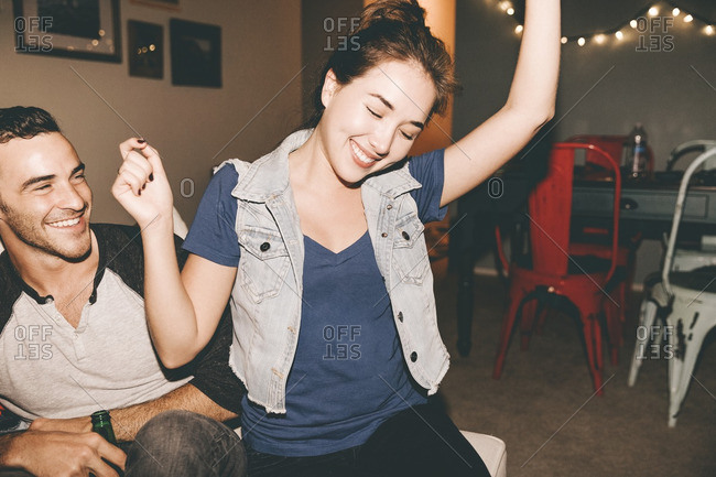 Happy man looking at cheerful woman dancing while sitting on sofa during house party