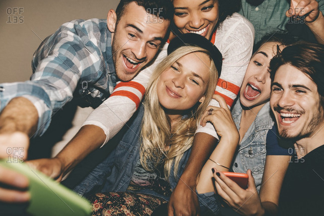 Multiethnic friends taking selfie through smart phone during house party
