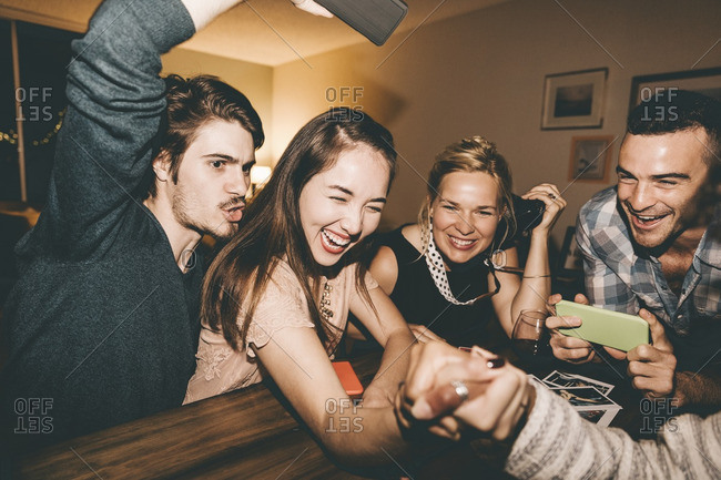 Cheerful female friends arm wrestling at table during house party