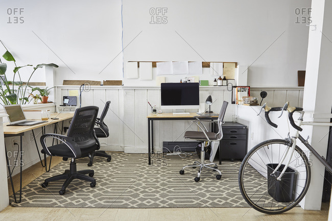 Chairs and computer against white wall in creative office