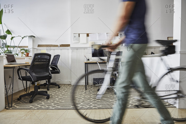 Blurred motion of businessman walking with bicycle in creative office
