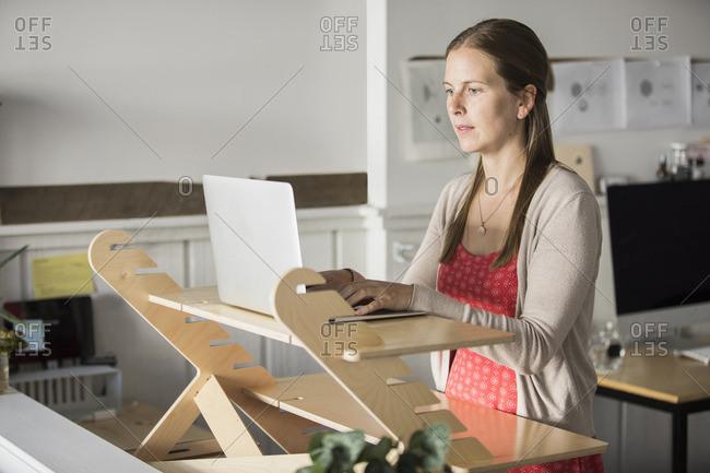 Businesswoman surfing internet on laptop in creative office