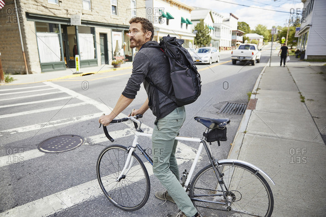Side view of businessman with bicycle waiting at crosswalk on road