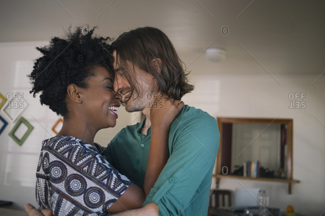 Cheerful multiethnic couple embracing while standing at home