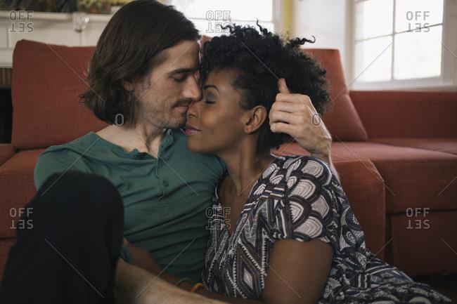Romantic multiethnic couple sitting against sofa in living room