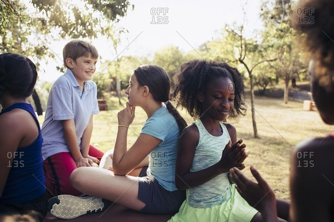 Multiethnic friends playing while sitting in park on sunny day