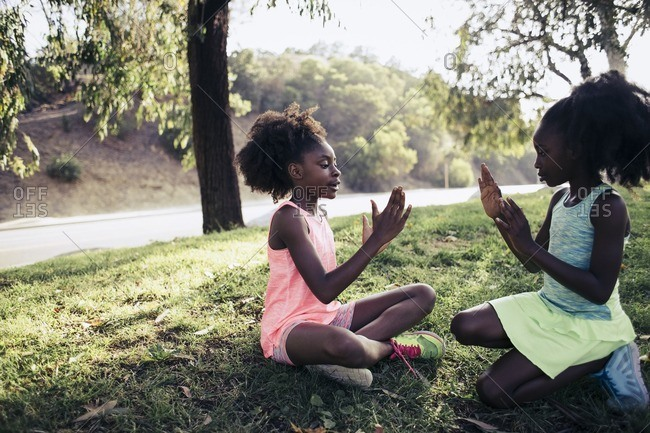 Full length of sisters playing clapping game while sitting on grass in park