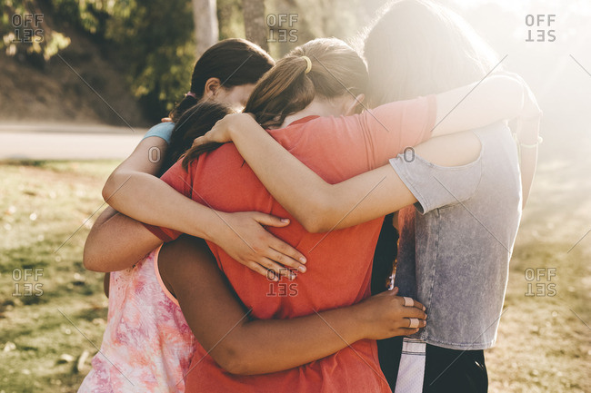 Girls forming huddle in park on sunny day