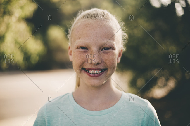 Portrait of girl with braces smiling in park