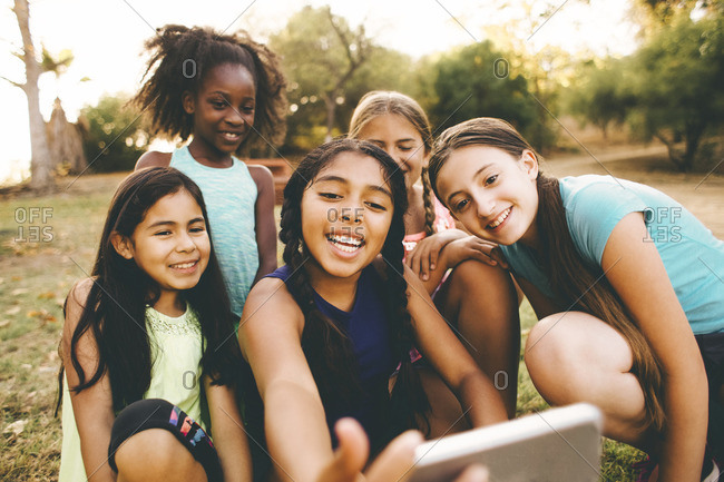 Happy girl with friends taking selfie through mobile phone in park